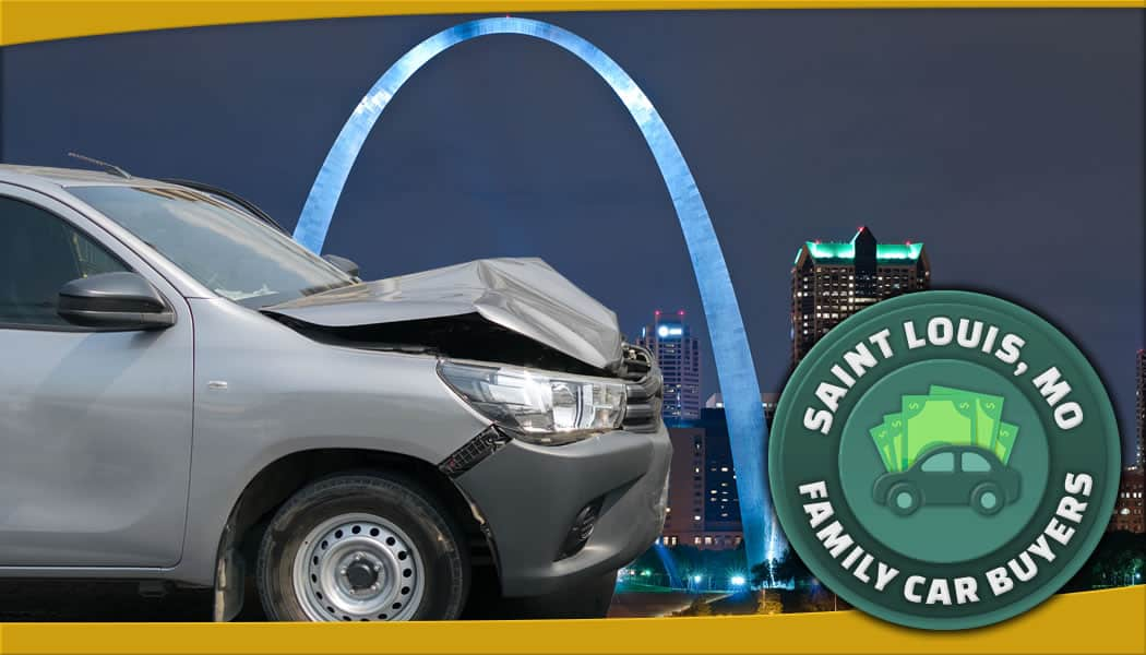 Grey dented car in front of Saint Louis arch from across the river along with service area emblem