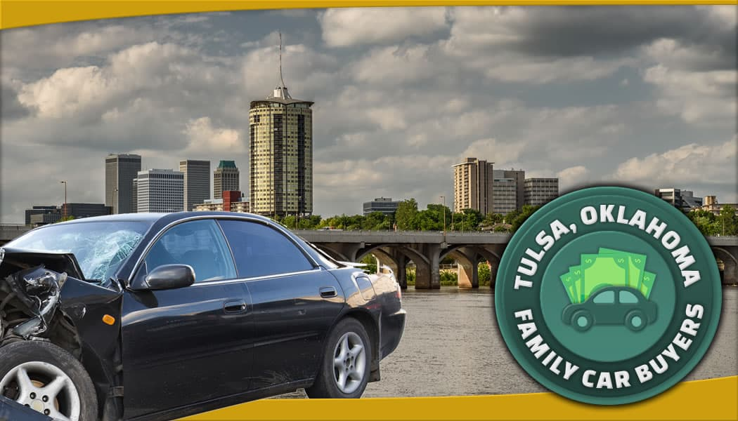 Black car with smashed front-end in foreground of Tulsa downtown and water with FCB service area emblem.